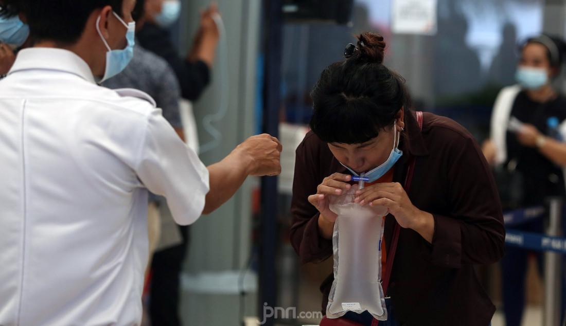 Petugas kesehatan di Stasiun Pasar Senen, Jakarta Pusat, Jumat (5/2), memberikan petunjuk kepada calon penumpang kereta api tentang cara menggunakan GeNose untuk tes Covid-19. Kementerian Perhubungan telah menetapkan hasil tes GeNose sebagai syarat perjalanan menggunakan kereta api jarak jauh. Foto: Ricardo - JPNN.com