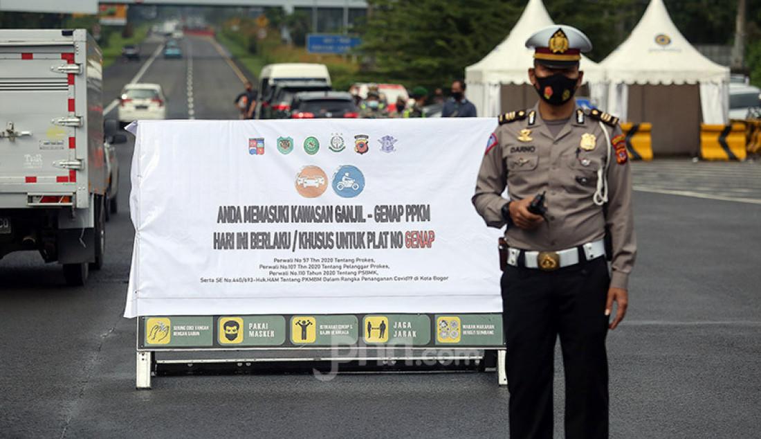 Petugas kepolisian memantau pelat nomor kendaraan di Kota Bogor, Sabtu (7/2). Pemerintah Kota Bogor memberlakukan sistem ganjil-genap pada 6-7 Februari 2021 dalam rangka mengurangi kerumunan dan mencegah penularan Covid-19. Foto: Ricardo - JPNN.com