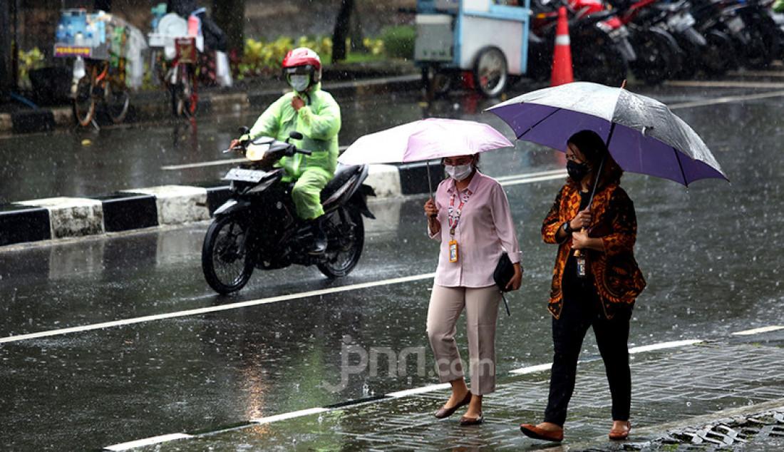 Warga menggunakan payung saat hujan mengguyur kawasan Kuningan, Jakarta Selatan, Selasa (16/2). Badan Meteorologi, Klimatologi, dan Geofisika (BMKG) memprakirakan cuaca ekstrem akan melanda wilayah Jabodetabek pada 15-21 Februari 2021. Foto: Ricardo - JPNN.com