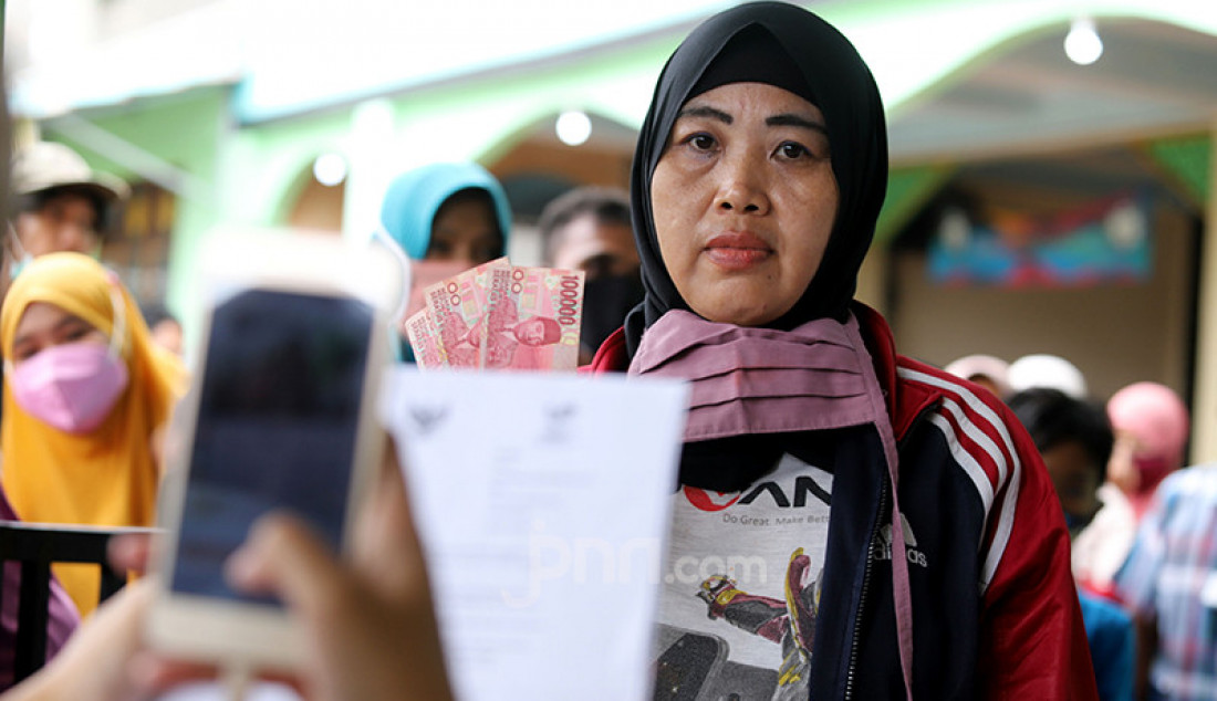 Seorang warga saat mengantre pencairan dana Bantuan Sosial Tunai (BST) sebesar Rp 300 ribu di halaman Masjid Jami' Al-Hidayah di RW 01 Bedahan, Kota Depok, Selasa (16/2). Sebanyak 159.470 Keluarga Penerima Manfaat (KPM) di Kota Depok menerima BST yang disalurkan melalui PT Pos Indonesia. Foto: Ricardo - JPNN.com