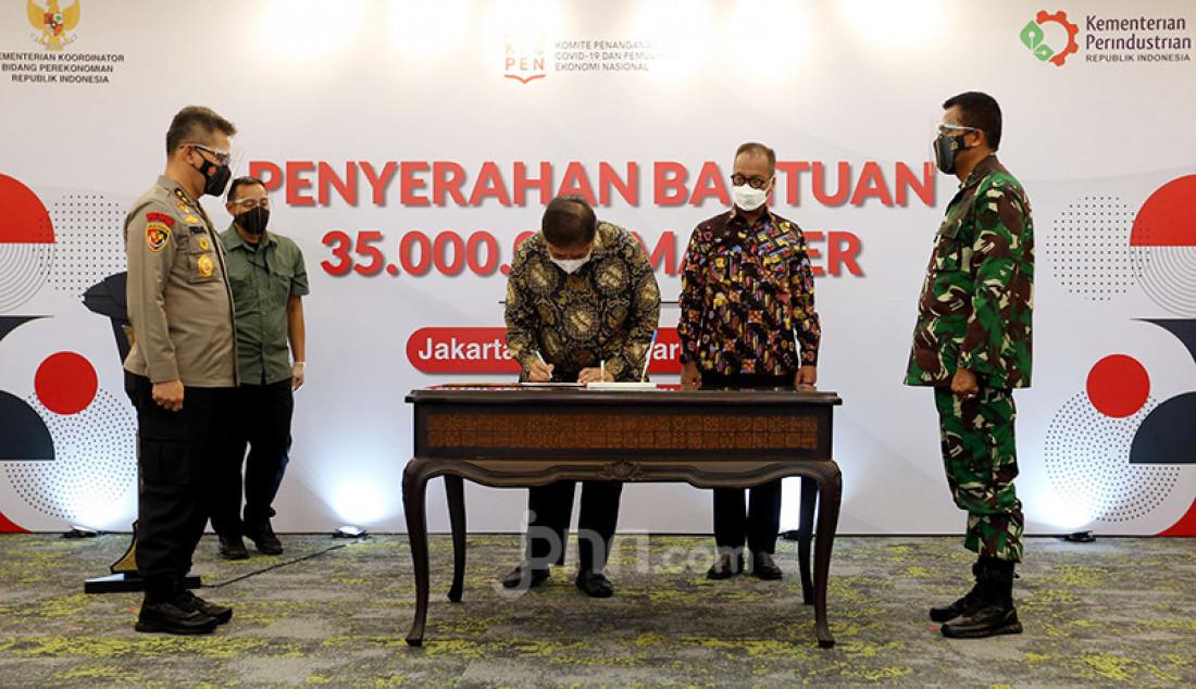 Menko Perekonomian Airlangga Hartarto menandatangani berita acara penyerahan bantuan 35 juta masker dari Kementerian Perindustrian untuk masyarakat melalui TNI dan Polri di Jakarta, Rabu (24/2). Foto: Ricardo - JPNN.com