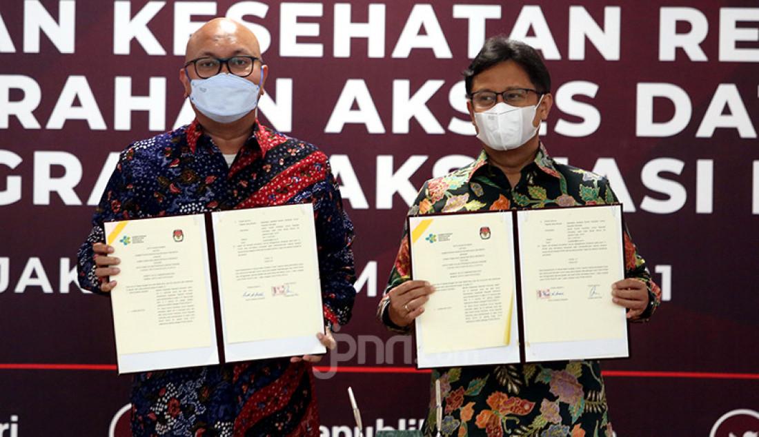 Pelaksana tugas (Plt) Ketua KPU RI Ilham Saputra (kiri) dan Menkes Budi Gunadi berfoto bersama di Jakarta, Selasa (2/3) usai penandatanganan kerja sama dalam rangka penanggulangan pandemi COVID-19 dan penyerahan akses data pemilih untuk Progam Vaksinasi Nasional. Foto: Ricardo - JPNN.com