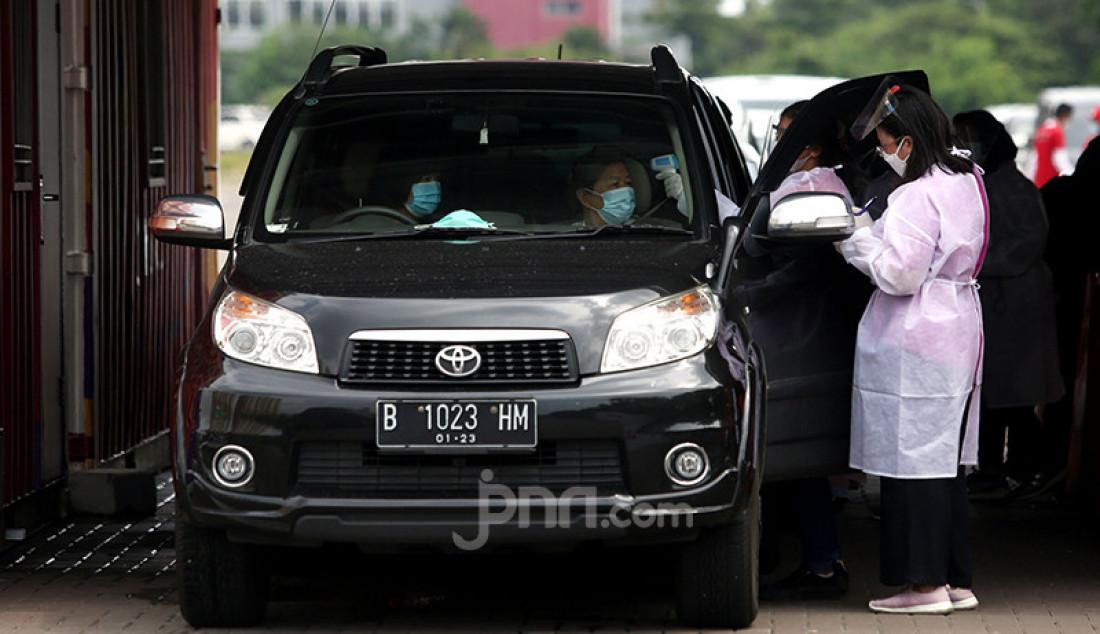 Petugas kesehatan menyuntikkan vaksin Covid-19 kepada lansia melalui layanan drive thru di kawasan Kemayoran, Jakarta Pusat, Senin (8/3). Vaksinasi Covid-19 bagi para manula melalui layanan drive thru tersebut merupakan hasil kerja sama Kementerian Kesehatan dan Halodoc. Foto: Ricardo - JPNN.com
