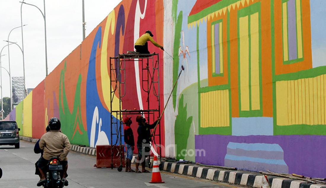 Seniman mengerjakan mural berkonsep adat Betawi di Flyover Gaplek, Pamulang, Tangerang Selatan, Banten, Rabu (9/3). Mural tersebut sebagai upaya melestarikan budaya dan menjaga kebersihan kota dari aksi vandalistis di wilayah Tangsel. Foto: Ricardo - JPNN.com