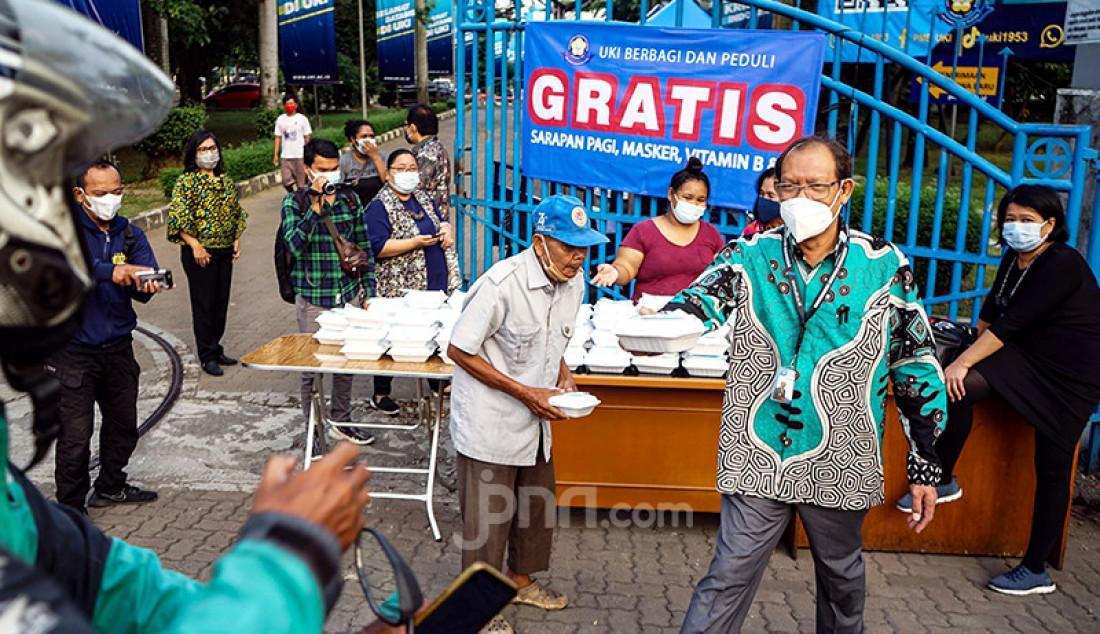 Sejumlah civitas akademi Universitas Kristen Indonesia menggelar kegiatan UKI Peduli dan Berbagi di sekitar kampusnya di Cawang, Jakarta Timur, Kamis (18/3). Melalui kegiatan itu, UKI membagikan makanan, masker, dan vitamin kepada warga yang melintas di sekitar kampus. Foto: Ricardo - JPNN.com