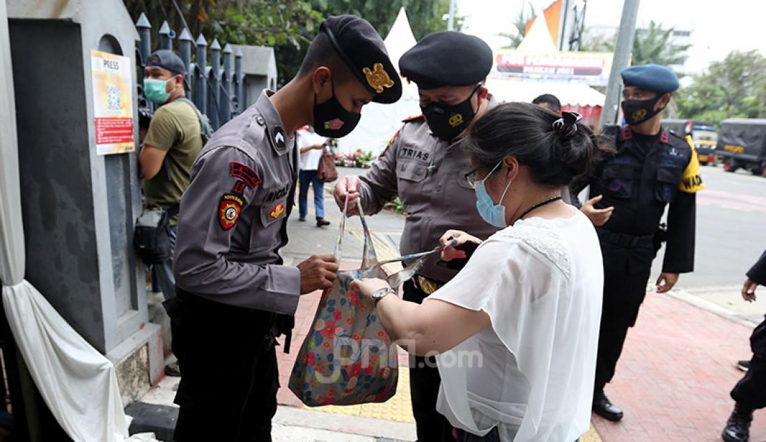 Petugas memeriksa barang bawaan warga yang memasuki Gereja Katedral, Jakarta, Kamis (1/4). Sebanyak 150 personel gabungan TNI, Polri, dan Satpol PP melakukan pengamanan jelang rangkaian perayaan Paskah. Foto: Ricardo - JPNN.com