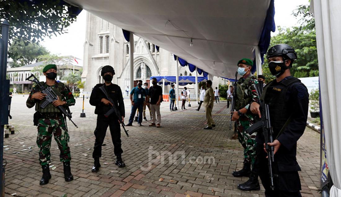 Petugas TNI-Polri melakukan penjagaan di depan Gereja Katedral, Jakarta, Kamis (1/4). Sebanyak 150 personel gabungan TNI, Polri, dan Satpol PP melakukan pengamanan jelang rangkaian perayaan Paskah. Foto: Ricardo - JPNN.com