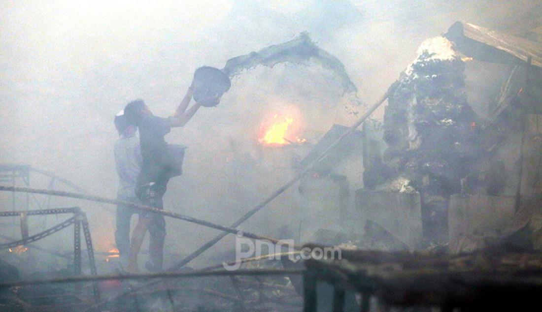 Pedagang mencoba memadamkan api yang melahap Pasar Kambing di Tanah Abang, Jakarta Pusat, Kamis (8/4). Sebanyak 17 unit branwir dan 85 personel pemadam kebakaran dikerahkan untuk memadamkan api yang menghanguskan ratusan lapak dan puluhan kios di Pasar Kambing. Foto: Ricardo - JPNN.com