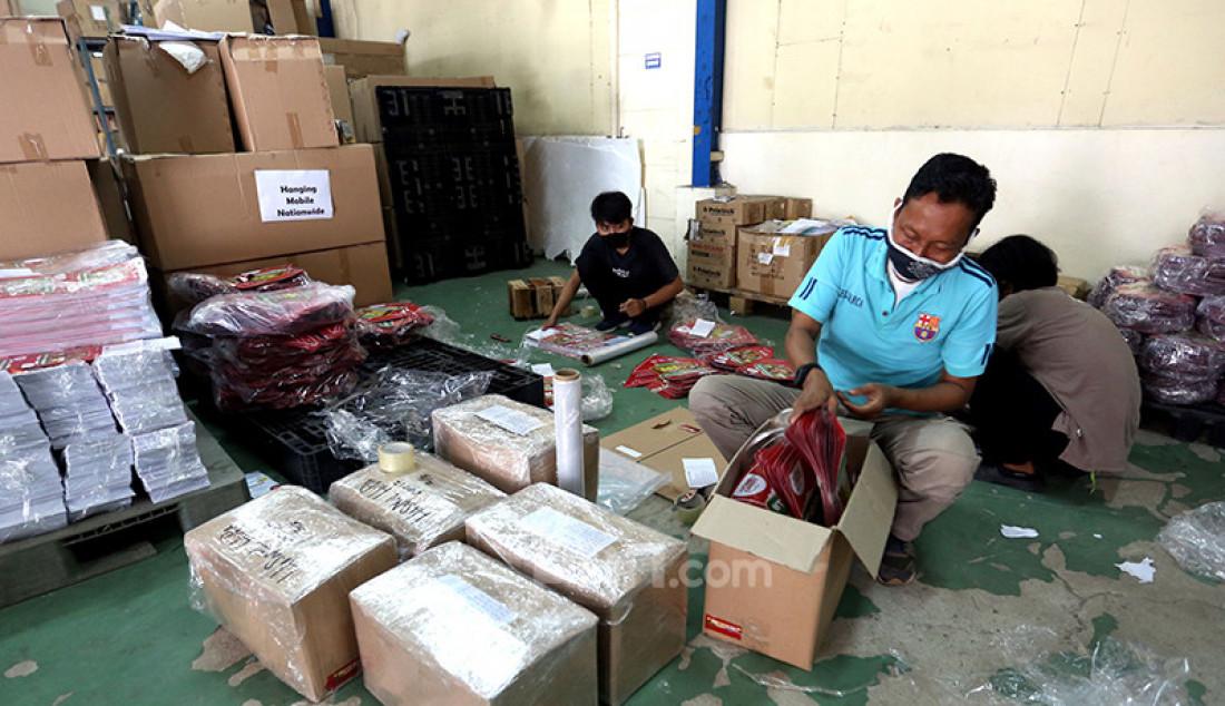 Pegawai di gudang NCS Logistik, Jakarta, Sabtu (17/4), mengemas paket barang yang akan dikirim ke luar kota. Angka pengiriman barang pada pekan pertama Ramadan meningkat lebih dari 100 persen seiring rencana pemerintah menyubsidi ongkos kirim (ongkir) pada Hari Belanja Online Nasional (Harbolnas) sebelum Lebaran. Foto: Ricardo - JPNN.com