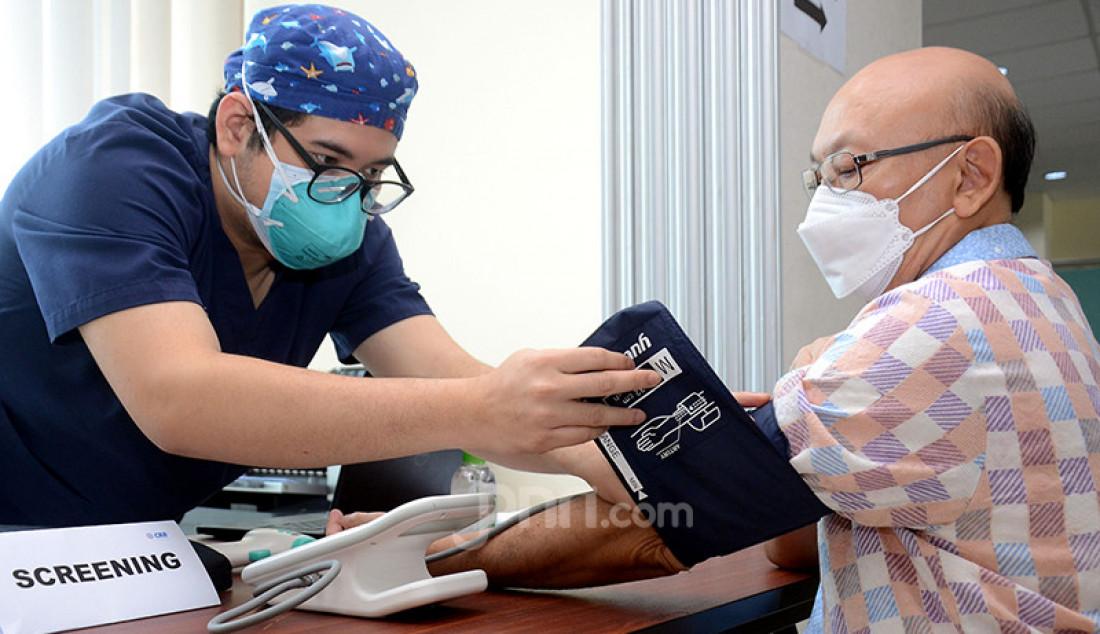 Petugas kesehatan menyuntikkan vaksin Covid-19 kepada lansia di Jakarta, Selasa (27/4). Pemerintah melalui Otoritas Jasa Keuangan (OJK) mengadakan vaksinasi Covid-19 bagi para lansia dalam rangka program Vaksinasi Industri Keuangan Non-Bank. Foto: Ricardo - JPNN.com