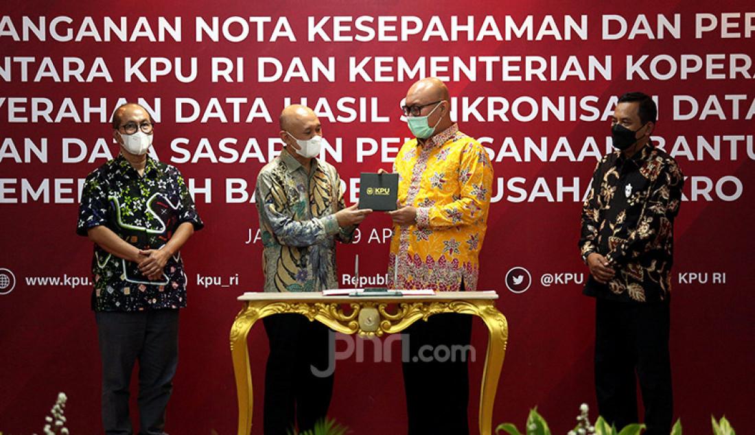 Menteri Koperasi dan UKM Teten Masduki bersama Ketua KPU Ilham Saputra (berdiri di tengah) pada penandatanganan perjanjian kerja sama tentang pemanfaatan data pemilih untuk pendataan sasaran pelaksanaan bantuan pemerintah bagi pelaku usaha mikro dalam rangka program Pemulihan Ekonomi Nasional (PEN) di Jakarta, Kamis (29/4). Foto: Ricardo - JPNN.com