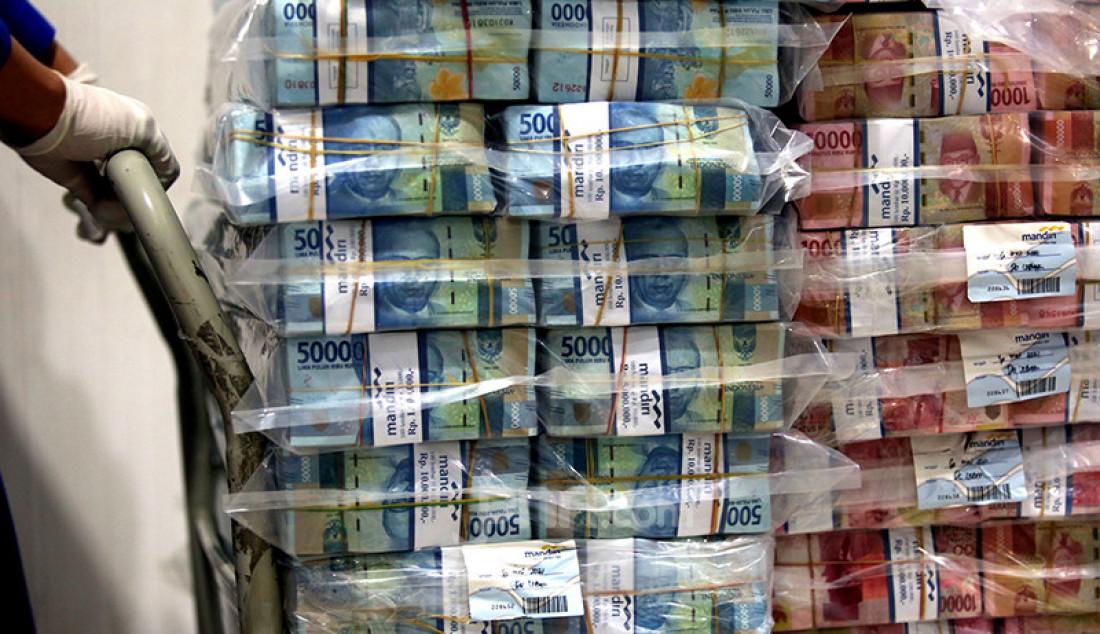 Karyawan Bank Mandiri merapikan tumpukan uang tunai pecahan kecil dan besar di cash pooling bank BUMN itu di Jakarta, Jumat (7/5). Bank Mandiri menyiapkan uang tunai sebesar Rp 20,8 triliun untuk mengantisipasi peningkatan kebutuhan masyarakat akan duit cash pada periode libur Idulfitri 1442 H. Foto: Ricardo - JPNN.com
