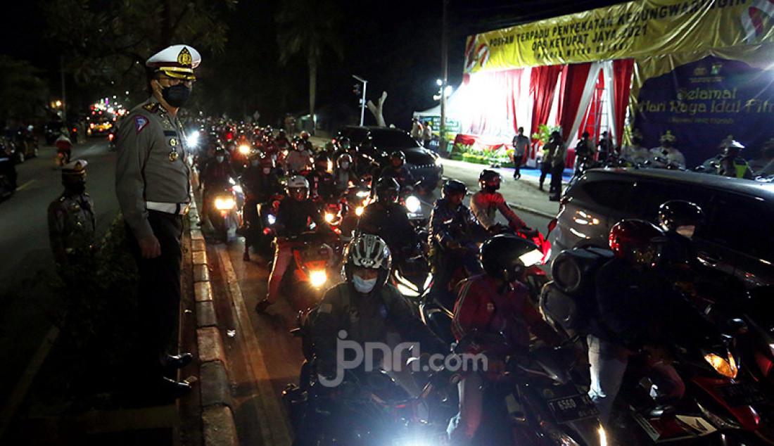 Aparat Polri memantau para pengendara sepeda motor di titik penyekatan perbatasan Kabupaten Bekasi dan Kabupaten Karawang, Jawa Barat, Senin malam (10/5). Penyekatan itu merupakan tindak lanjut atas kebijakan pemerintah tentang larangan mudik yang berlaku 6-17 Mei 2021. Foto: Ricardo - JPNN.com
