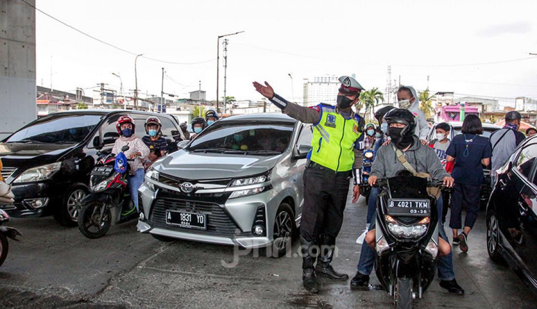 Petugas kepolisian memberhentikan kendaraan di pintu masuk Ancol Taman Impian, Jakarta, Sabtu (15/5). Pengelola Ancol Taman Impian menutup seluruh area rekreasi dan wisata selama satu hari pada Sabtu (15/5) untuk dilakukan penyemprotan disinfektan dan evaluasi penguatan protokol kesehatan. Foto: Ricardo - JPNN.com